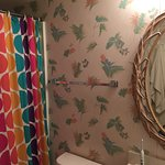 Outdated wallpaper, fixtures and shower curtain in a bathroom.