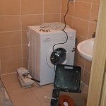 The Washing machine in the Shower Room under the workmens tools