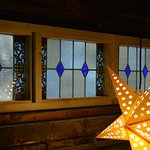 One of the illuminated stars against the stained glass transom