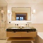 Badezimmer mit Waschtisch aus grünem Naturstein, Badewanne und Dusche