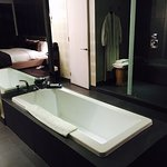 An open bathtub, next to the bed!