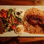 Roast chicken atop rice with mixed vegetable salad