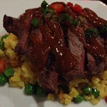 Grilled venison, creamy saffron rice & peas and balsamic tomato glaze