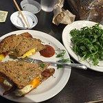Breakfast sandwich on Crazy Grain Bread with a side of greens.