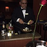 The waiter creates the desert at table side in elegance and old Style