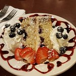 Lemony cake with berries served with raspberry coulis and fresh fruits.
