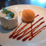 Lemon and lime cheesecake with orange sorbet and strawberry sauce