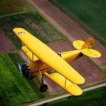 Waco Biplane flying over Wisconsin farmland.