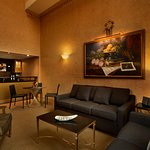 La Lune Penthouse living room with bar. Suite offers an outdoor patio with seating & views.