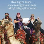 Our awesome guests Erica , Sarah and Eisha at the Pyramids in Cairo. holding Real Egypt Tours si