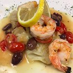 Fresh Cod topped with grilled shrimp with cherry tomatoes and Kalamata olives in a white wine le