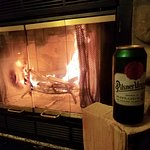 Enjoying a beer in front of the fire.