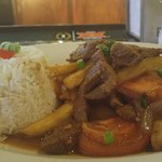 Lomo Saltado- strips of beef sirloin, French-cut potatoes, tomato and onions served with white r