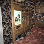 The bed enclosed with elaborate wooden screens