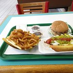 Char burger, hot dog and fries with some onion rings