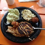 crabcake on top of fish filet, hush puppies, coleslaw, and potato slad