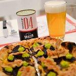 Pizza con patate viola, cheddar, emulsione di uovo e prezzemolo, bacon croccante