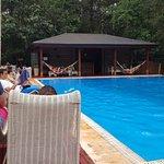 Hay reposeras, sillones y hamacas junto a la piscina. Relax total