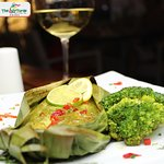 African Smoked Fish herb marinated, oven roasted in a banana leaf with a creamy coconut sauce