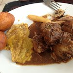 brown stew chicken with tostones (green plantain) and festival dumplings (fried bread)