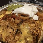 Nachos with spiced chicken, refried beans, yellow cheese, onions, guac, and sour cream. Amazing!