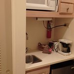 Mini fridge, sink, microwave, utensils, some dishes, cutting board