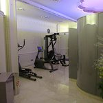 La salle de fitness avec la cabine du sauna au milieu.