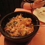 Vol de piedra caliente con base de arroz, verduras y huevo crudo en el centro.