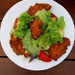 Breaded chicken pieces with salad, new potatoes and pesto