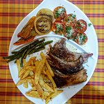 lamb with french fries, grilled onions and tomatoes with parmesan