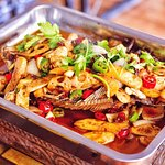 Roast fish including potatoes, stick rice, chilli and lotus root slices