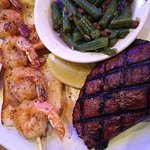 Sirloin steak with shrimp over rolls with garlic sauce and green beans with bacon.