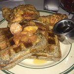 Two pieces of fried chicken and two buckwheat waffles topped with cinnamon butter & baked apples