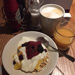 Muesli, no fat yogurt, dried fruit and coulis with costa coffee latte and OJ with a dash of cran