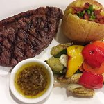 Beef steak with garlic sauce, fried vegetables and baked potato