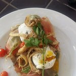 Poached eggs served on ciabatta bread topped with parma ham and oyster mushroms