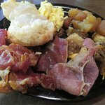 Scrambled eggs, baked apples, ham, bacon, potatoes with onions and cheese