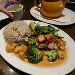 Thai red curry with tofu, with a pot and cup of jasmine green tea in the background. Delicious!