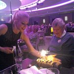 Entertainment staff bringing John an 80th birthday cake