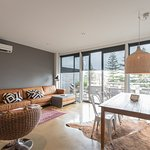 Aquabelle Two's dining living area overlooks bay from outdoor terrace