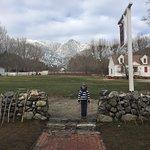 nephew posing outside of Hawk's Head, snowy mountains in background