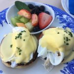 Eggs Benedict with a side of fruit
