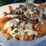 Potato Nachos (Pulled Pork on seasoned potato spirals and smothered in a creamy cheese sauce)
