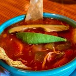 Chicken tortilla soup with shredded chicken, large tender vegetables and garnished with avocado.