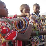 Maasai girls selling beads at camp fence