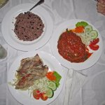 Pork and barbecue with large dish of black beans and rice