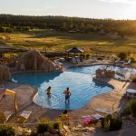 Sunset view over the pool area with water slides and jacuzzi tubs.