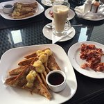 French toast with bananas, side of bacon, and cafe latte