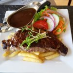 Porterhouse steak with salad and chips.