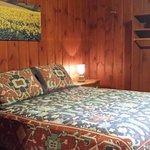 Room with queen size bed and double/full size bunks.